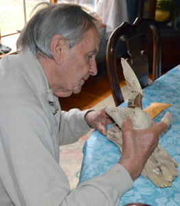 Artist Ray Tameo positions a carving in progress to a piece of drift wood.